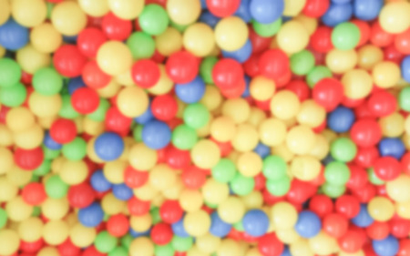 Defocused background with colorful plastic balls in childrens playground pool. Intentionally blurred post production for bokeh effect Stockfoto
