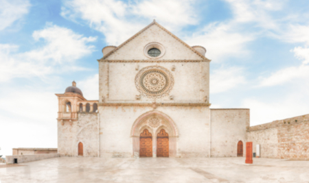 Defocused background with facade of the Papal Basilica of Saint Francis of Assisi, Italy. Intentionally blurred post production for bokeh effect