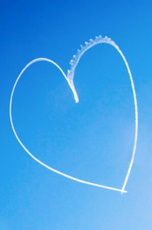 Romantic heart written in the blue sky by a small aircraft