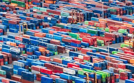 Textura hecha con una vista aérea sobre contenedores de carga apilados en un puerto comercial. Adecuado para ser utilizado como fondo.