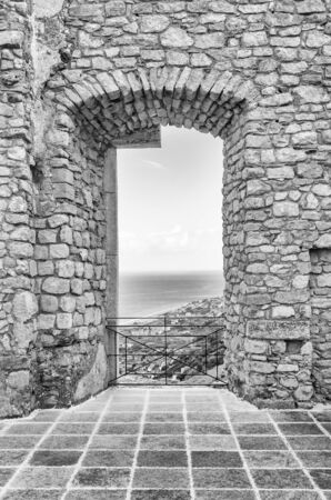 Ancient window from the ruins of an old castle with beautiful view over the sea Фото со стока
