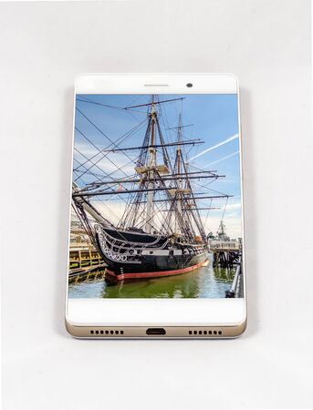 Modern smartphone with USS Constitution frigate docked in the Boston Harbor, USA. Concept for travel smartphone photography. All images in the composition are made by me and  available on my portfolio Фото со стока