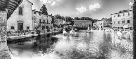 Panoramic view of the iconic medieval thermal baths, major landmark and sightseeing in the town of Bagno Vignoni, province of Siena, Tuscany, Italy Фото со стока