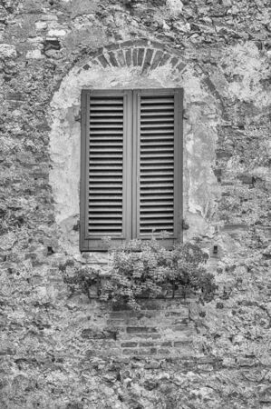Scenic window in the medieval architecture of San Gimignano, iconic town in the province of Siena, and one of the most visited place in Tuscany, Italy Фото со стока