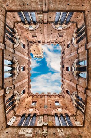 Scenic view from the bottom at the patio of Palazzo Pubblico, major landmark in Siena, Italy Редакционное