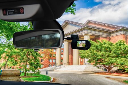 Looking through a dashcam car camera installed on a windshield with view of the Harvard University Campus, Cambridge, USA Фото со стока