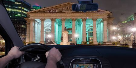 Driving a car at night towards the Royal Exchange Building, iconic landmark in London, UK