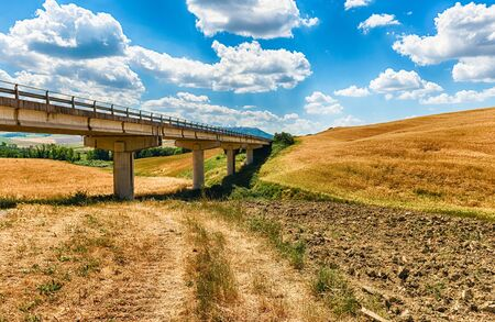 Highway crossing a landscape of dry fields in the countryside in Tuscany, Italy. Concept for agriculture and farmlands