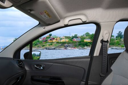 Looking through a car window with view over colorful houses on the shore of Oslo fjord, Oslo, Norway Imagens
