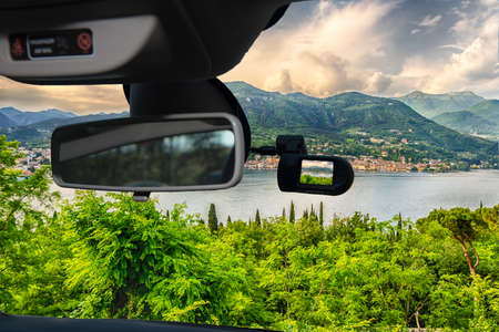Looking through a dashcam car camera installed on a windshield with view of the town of Salo, on the Lake Garda, Italy