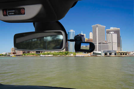 Looking through a dashcam car camera installed on a windshield with view of the financial district of of Manhattan, New York City, USA