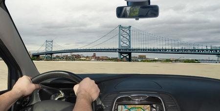 Driving a car towards Benjamin Franklin Bridge, iconic landmark in Philadelphia, Pennsylvania, USA