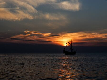 Saling boat in dramatic summer sunset at the evening Stock Photo