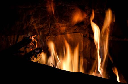 Closeup view of blazing and warming fireplace in the cold evening.