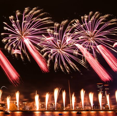 Gorgeous fire show. Exciting red and rose toned firework splashes exploding in the night. Banco de Imagens - 146356652