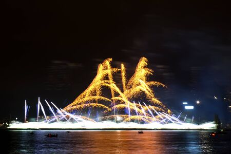 Gorgeous fire show. Exciting colourful firework splashes in form of waves exploding in the night. Banco de Imagens