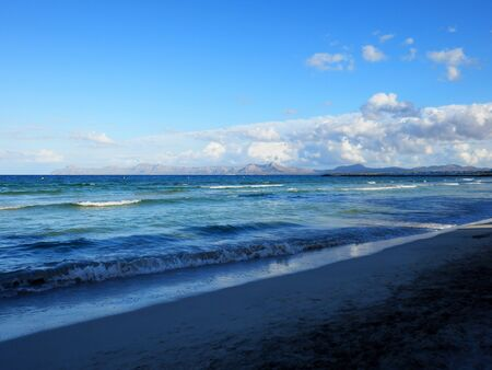 Alcudia beach in Mallorca island with gorgeous view on the warm crystal clear turquoise sea and the mountains. Banco de Imagens - 145747799