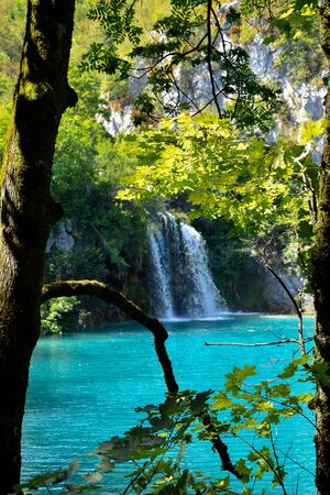Crystal clear turquoise water with small waterfall in September. Plitivce Lakes, Croatia. Banco de Imagens - 145925430