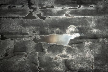 No people. Sky reflection in a puddle on the bad and cracked asphalt after the rain. Banco de Imagens - 146408482