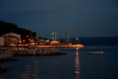 Calm and warm summer night the seacoast in Croatia with lights reflecting in the water. Banco de Imagens - 149038365