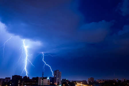 Bright flash of powerful lightning in the city at nighttime.