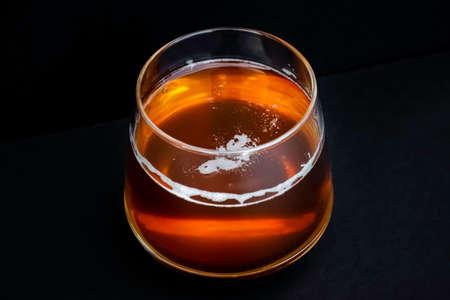 Glass of tasty beer. Light alcohol drink. Dark background.