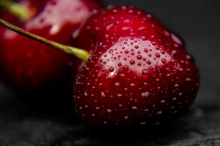Close up of fresh, healthy and wet sweet cherry berry with water drops on it.