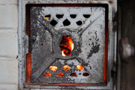 Blazing and warming fire in the stove through the closed door.
