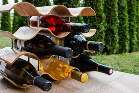 Collection of different wine bottles on the stand.