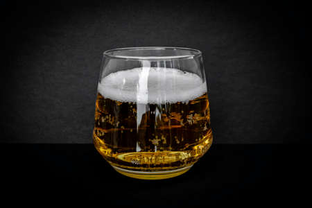 Glass of delicious beer. Light alcohol drink. Dark background.