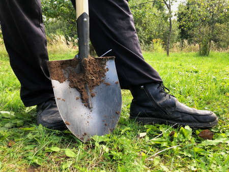 Farmer is standing with the shovel in the garden. Banco de Imagens