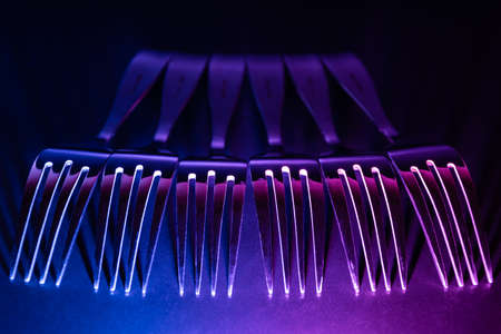 A set of forks in a raw with blue and violet coloured gradient led light in the dark. Banco de Imagens