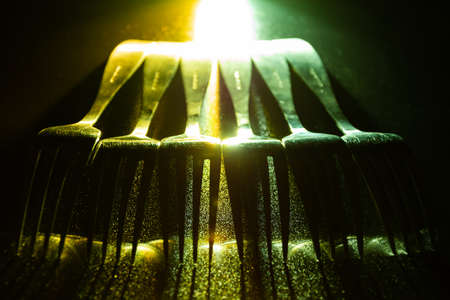 A set of forks in a raw with green and yellow contrast gradient led light. Banco de Imagens