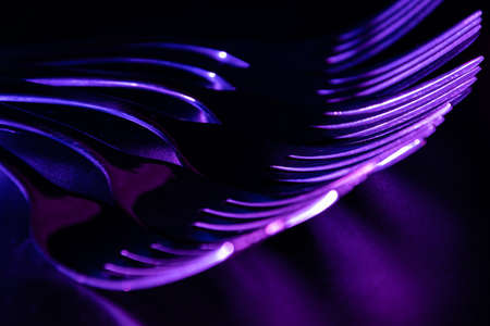 Set of forks in the dark with blue and violet coloured gradient led light.