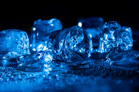 Melting frozen ice cubes illuminated with blue coloured LED light in the dark.