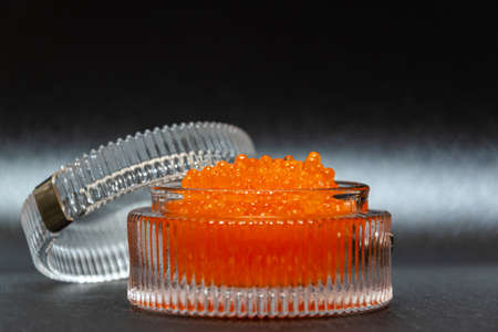 Close up of salted red caviar in a glassware on a black background. Banco de Imagens