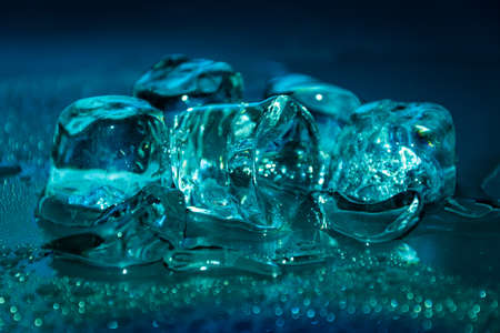 Melting frozen ice cubes illuminated with turquoise coloured LED light in the dark. Banco de Imagens