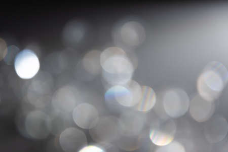 Abstract bokeh effect background in grey colours with rainbow rays. Banco de Imagens