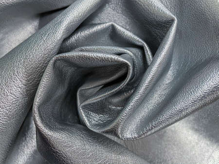 Close up of crumpled grained faux leather, dyed in silver colour.