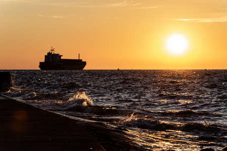 The silhouette of the ship on the horizon, going into the sunset.