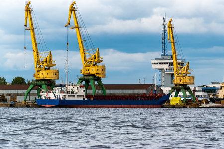 Coal industry. Yellow working coal cranes in the industrial port. Banco de Imagens