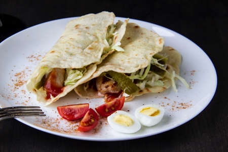 Sliced chicken with canned cucumbers and cabbage in sauce, wrapped in pita bread on a white plate. Delicious for lunch or dinner. Pieces of tomato and eggs on a plate with pita bread