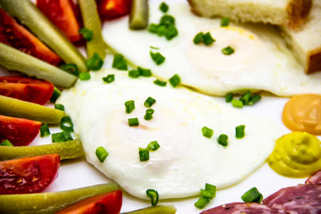 Delicious breakfast with eggs, salami, cucumbers, cherry tomatoes, slices of loaf, sauces and green onion on top on a white plate. Healthy and tasty meal for breakfast or lunch.