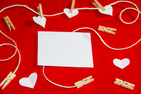 A red background from felt. A composition from heart, thread and clothespins. Background with place for write for valentines day and christmas. Standard-Bild