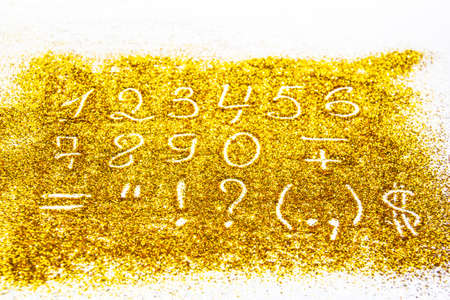 a composition with numbers and symbol on beautiful gold glitter. Background and texture of gold glitter. Luxury gold glitter sparkle shining texture background