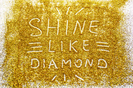 a composition with written a words shine like diamond on beautiful gold glitter. Background and texture of gold glitter. Luxury gold glitter sparkle shining texture background