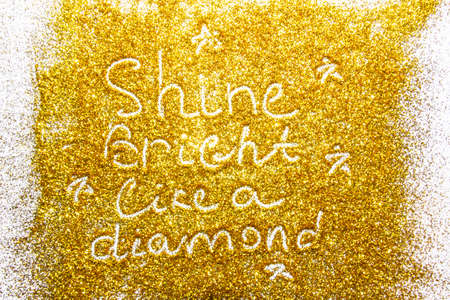 a composition with written a words shine bright like a diamond on beautiful gold glitter. Background and texture of gold glitter. Luxury gold glitter sparkle shining texture background