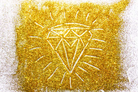 a composition with a diamond on beautiful gold glitter. Background and texture of gold glitter. Luxury gold glitter sparkle shining texture background