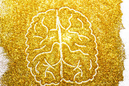 a composition with brain on beautiful gold glitter. Background and texture of gold glitter. Luxury gold glitter sparkle shining texture background