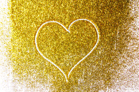 a composition with a heart on beautiful gold glitter. Background and texture of gold glitter. Luxury gold glitter sparkle shining texture background